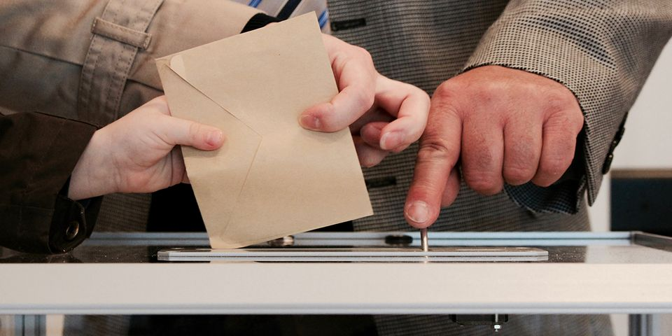 Hands putting envelope into ballot box